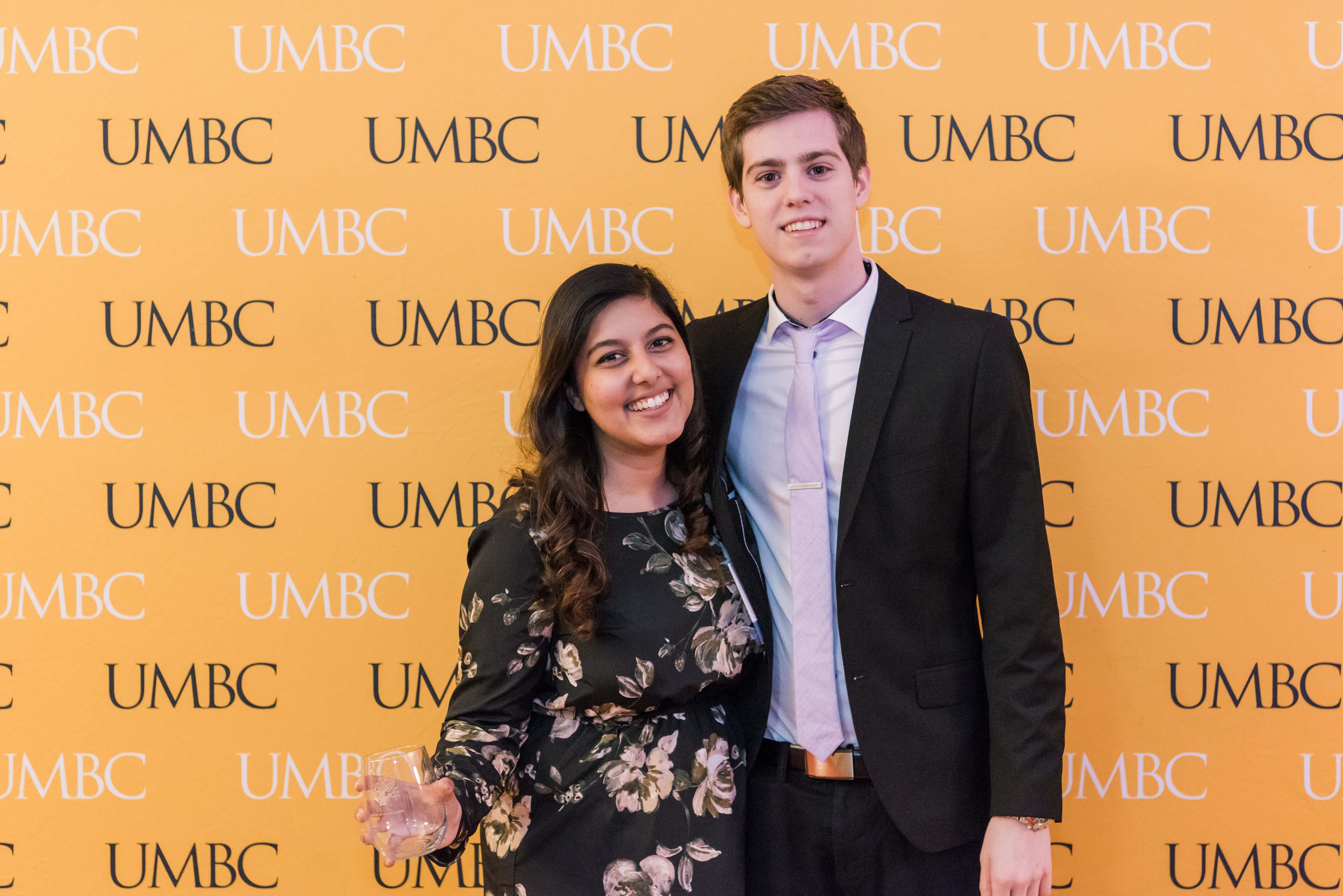 Poulomi poses with man wine glass in hand at UMBC wall for CYA event