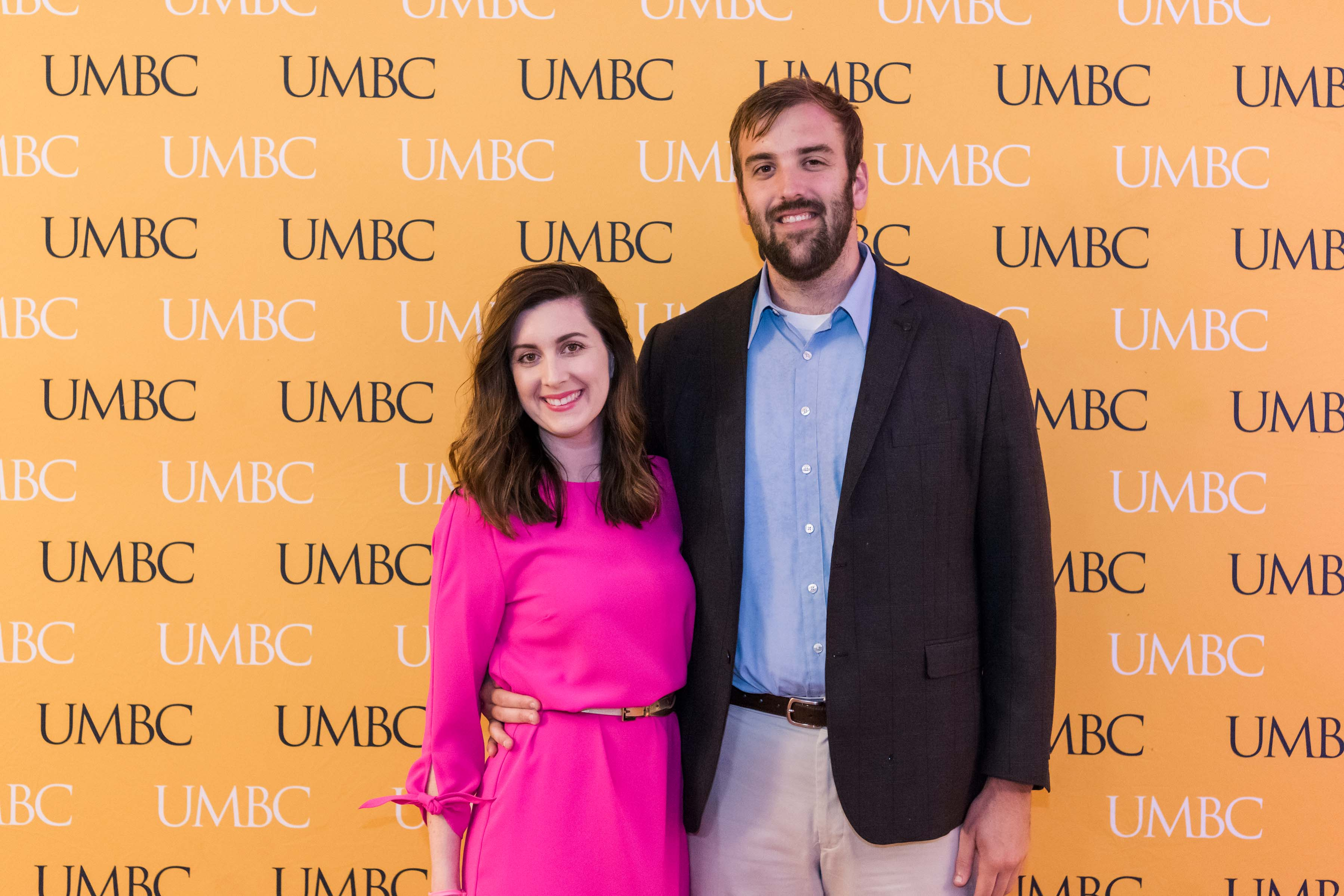 Man and woman pose with UMBC wall at wine tasting event