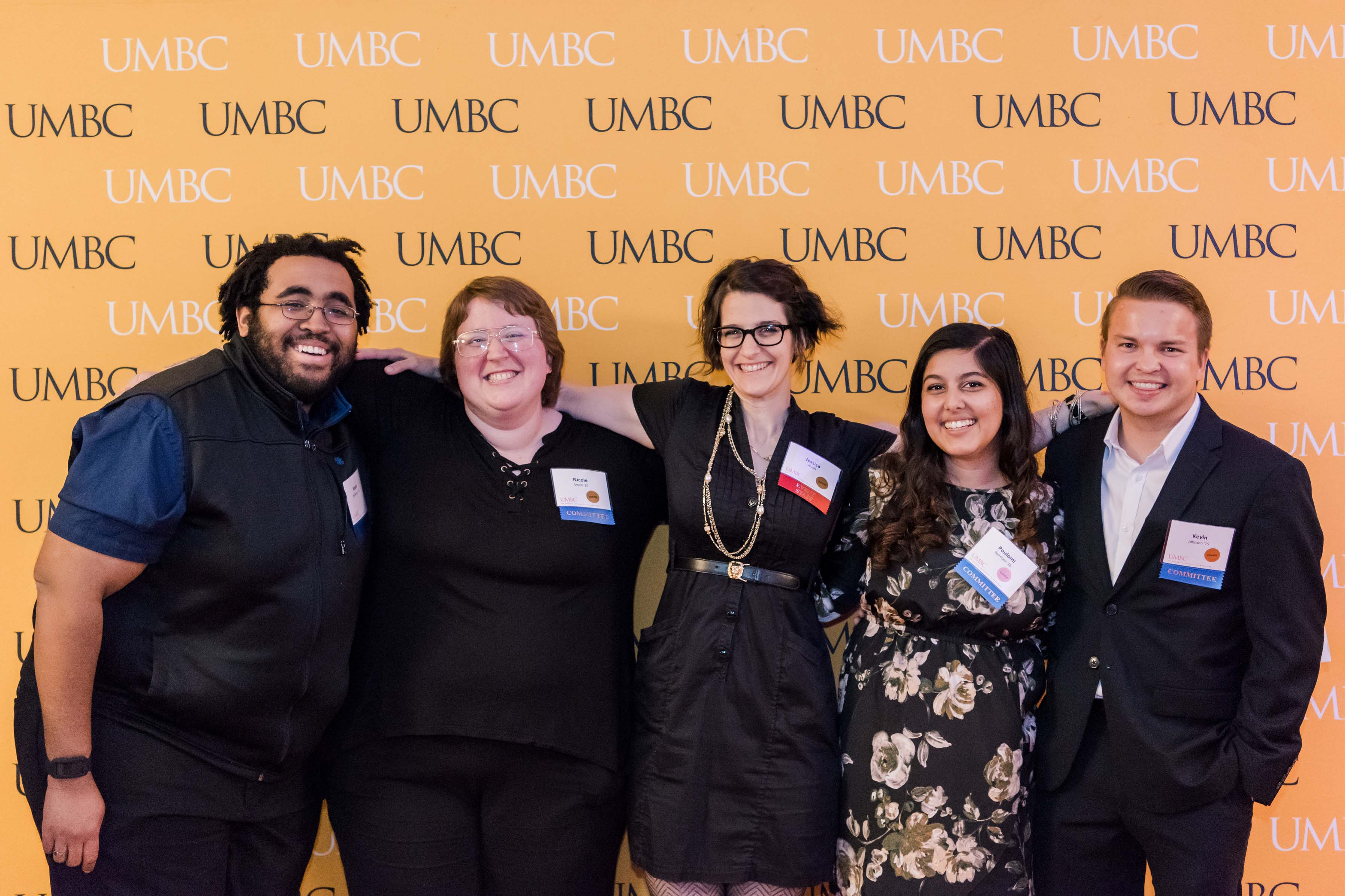 Group of five with name tags pose with UMBC wall at CYA wine tasting