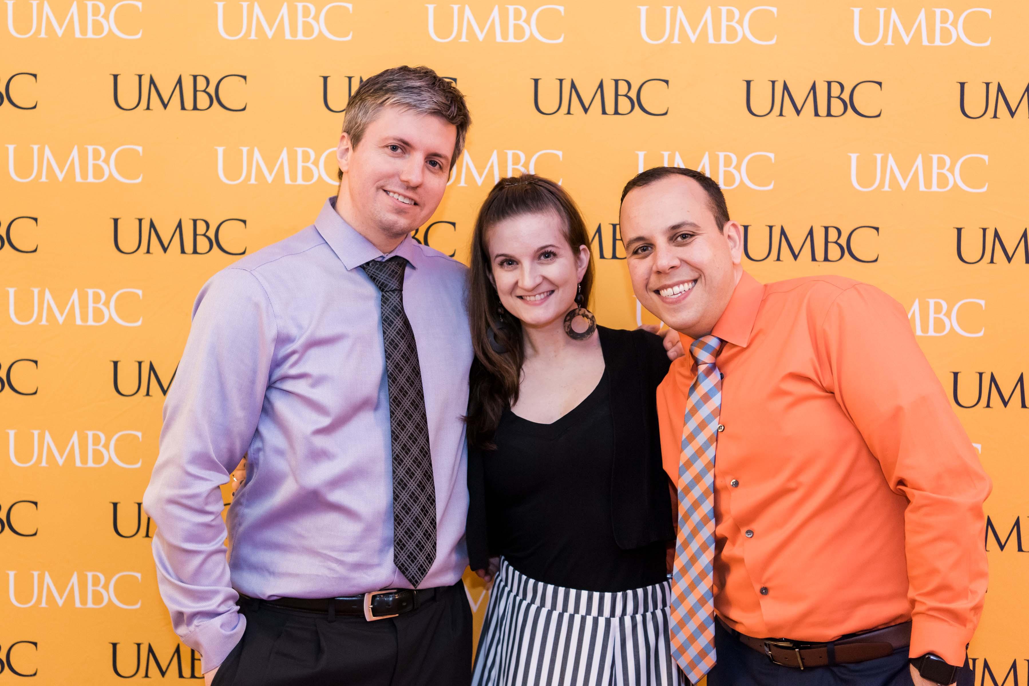 Three people pose with UMBC wall at wine tasting