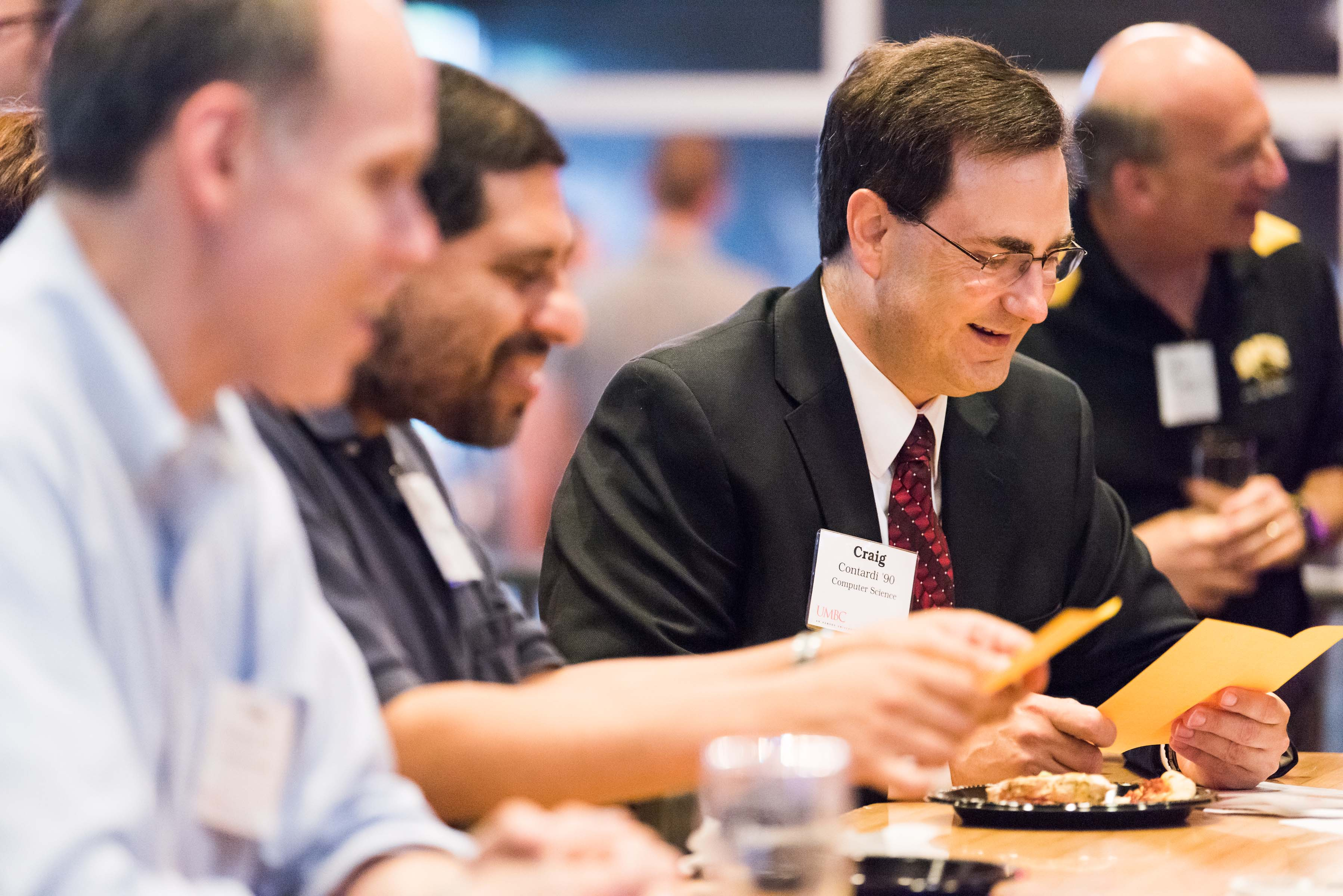 Craig and others smile down at papers at ITE happy hour