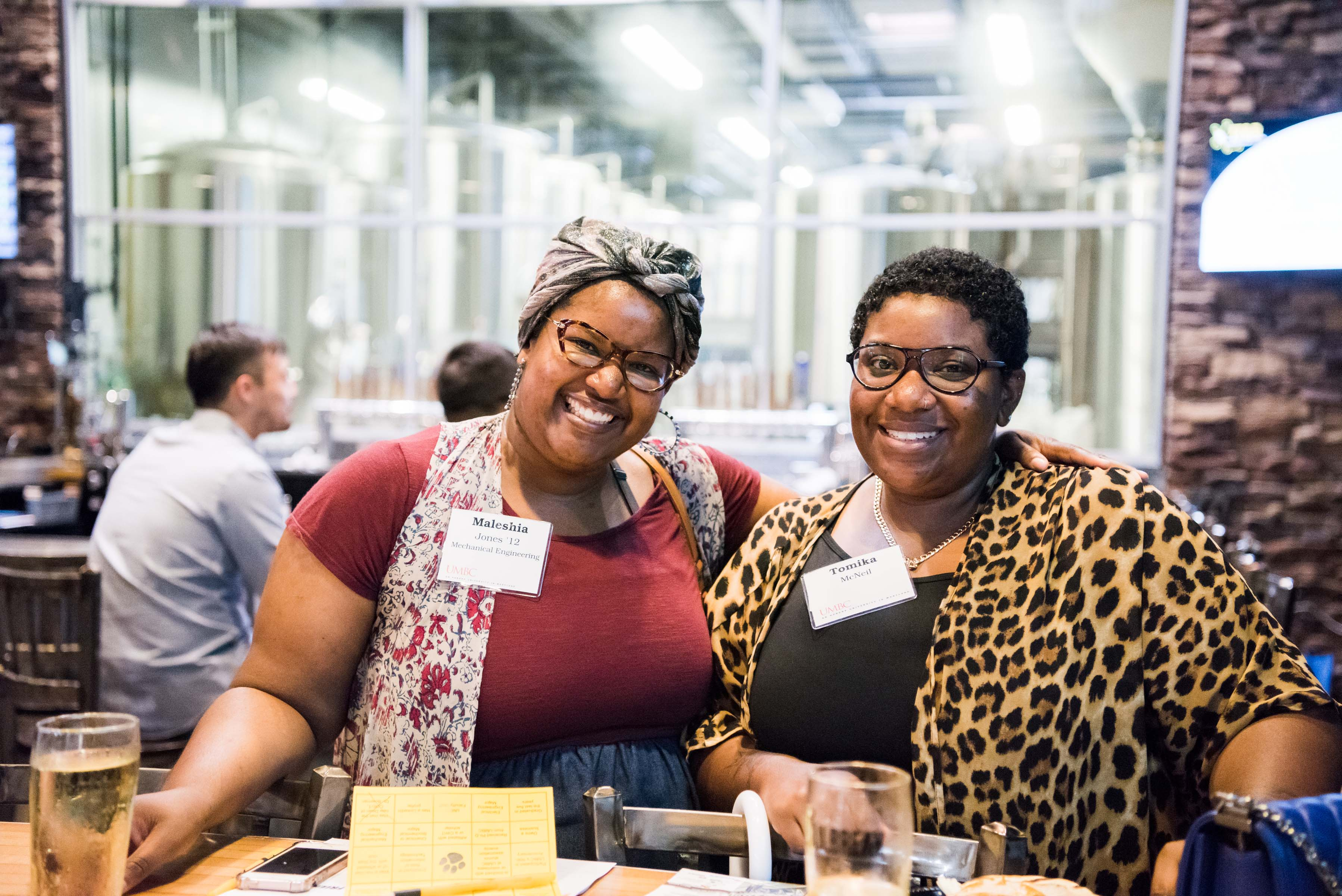 Two women in bold print and glasses smile together at ITE happy hour