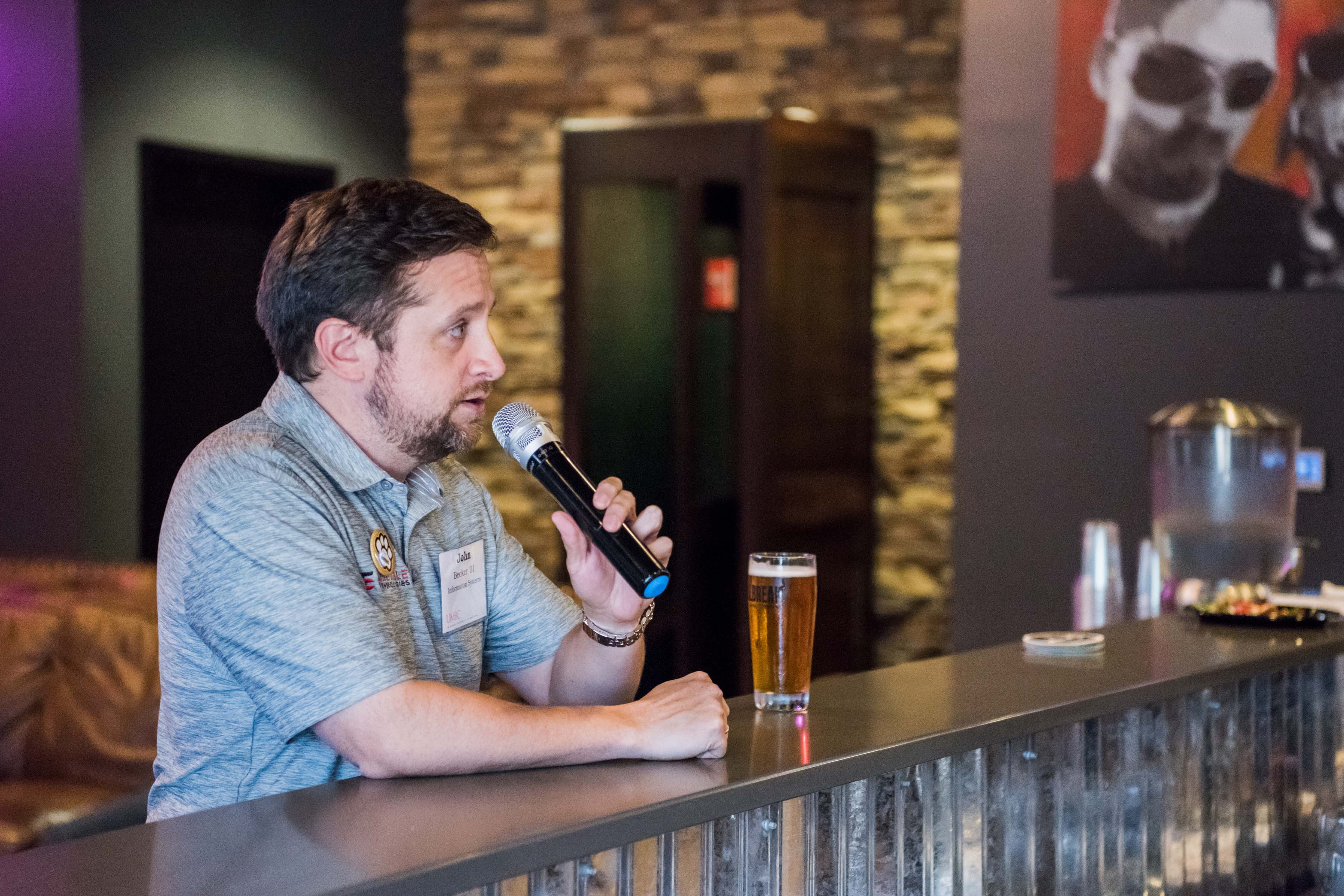 Man with microphone and beer glass gives speech for Jailbreak happy hour
