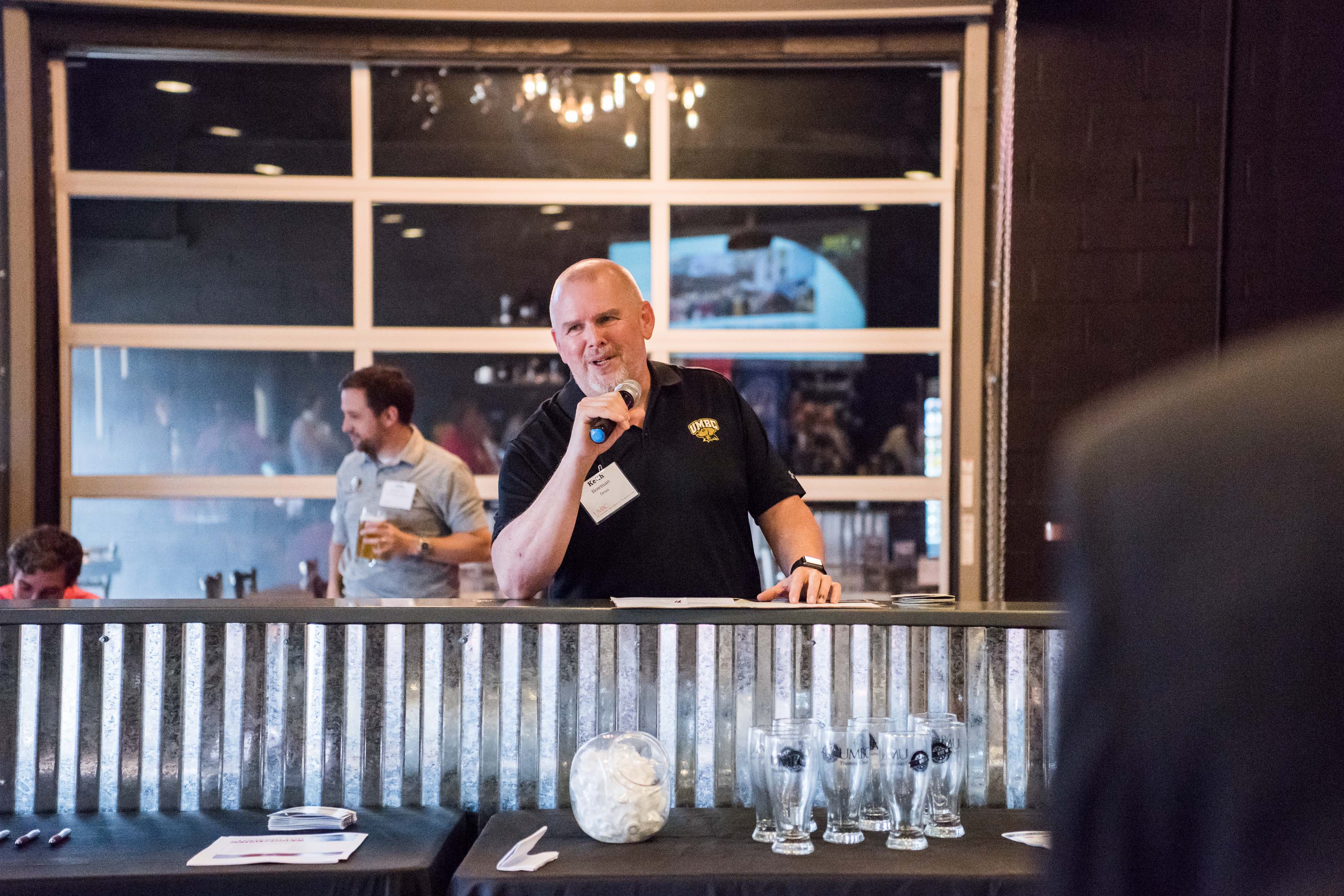 Man on microphone giving speech at Jailbreak brewing company happy hour