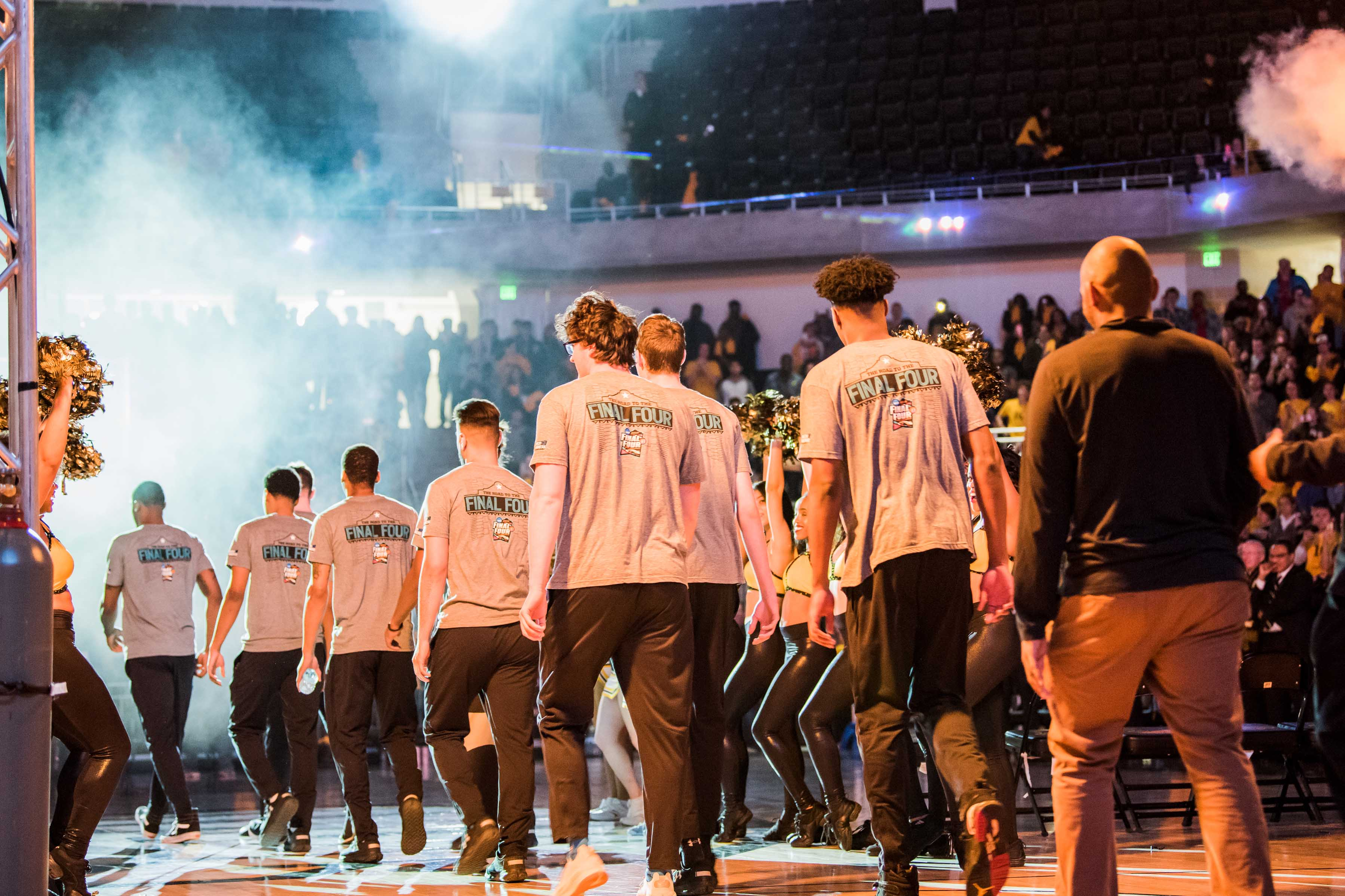 Men's basketball team walks out onto court with smoke