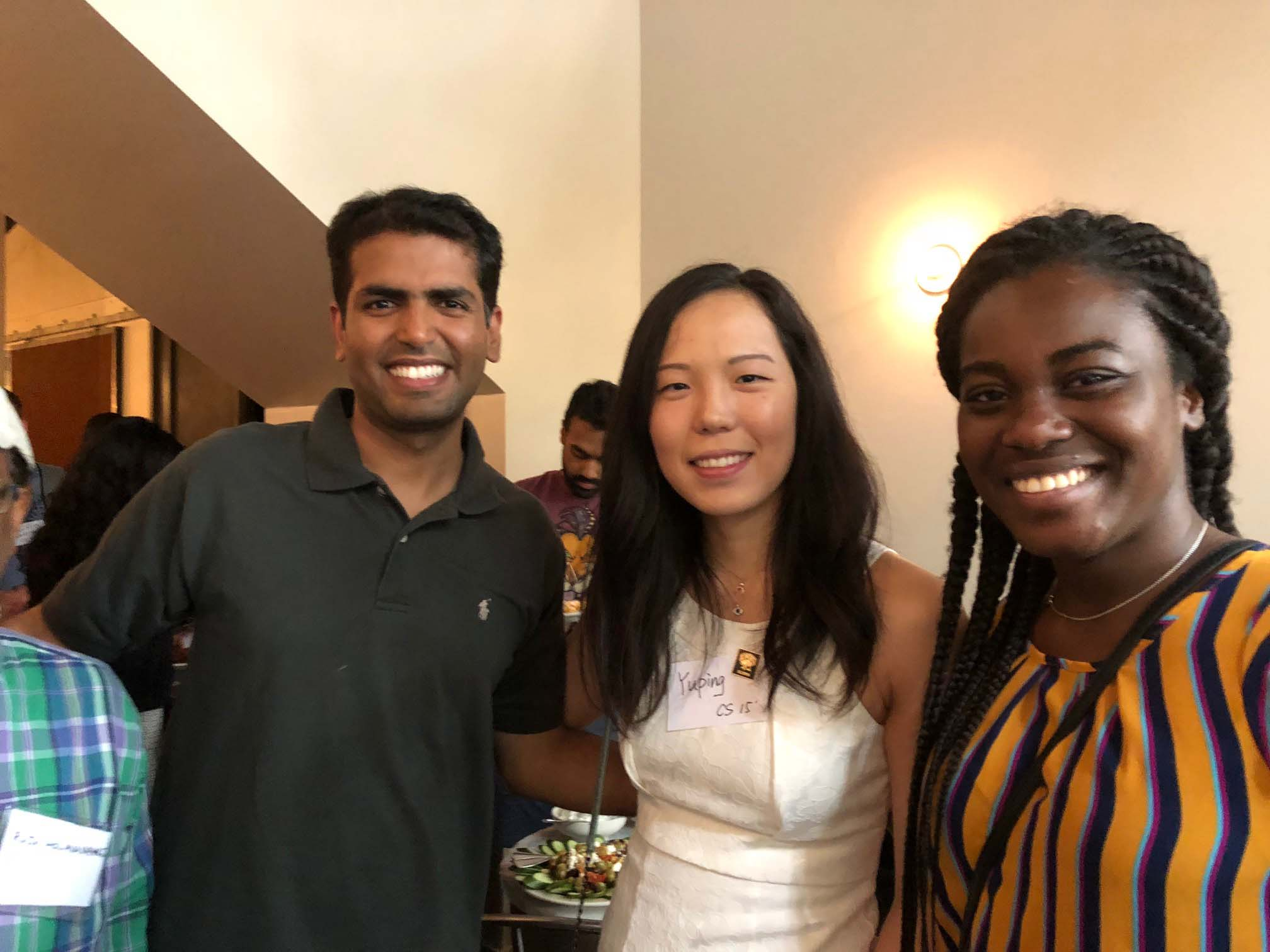 Three alumni smile together at Seattle networking event