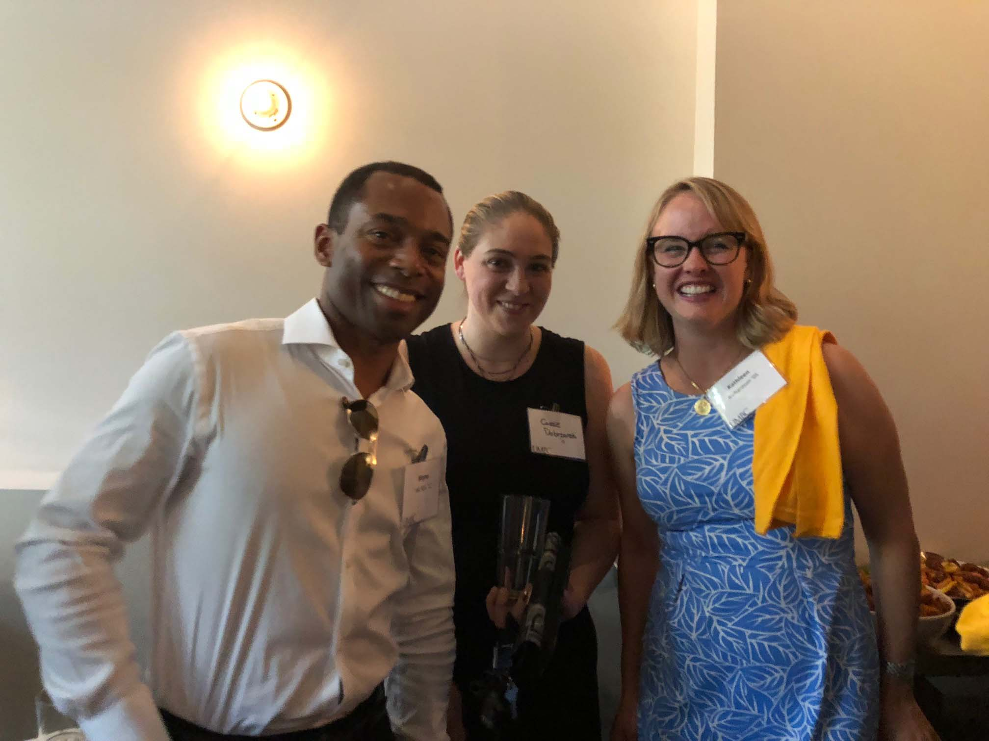 Three alumni smile together at networking event