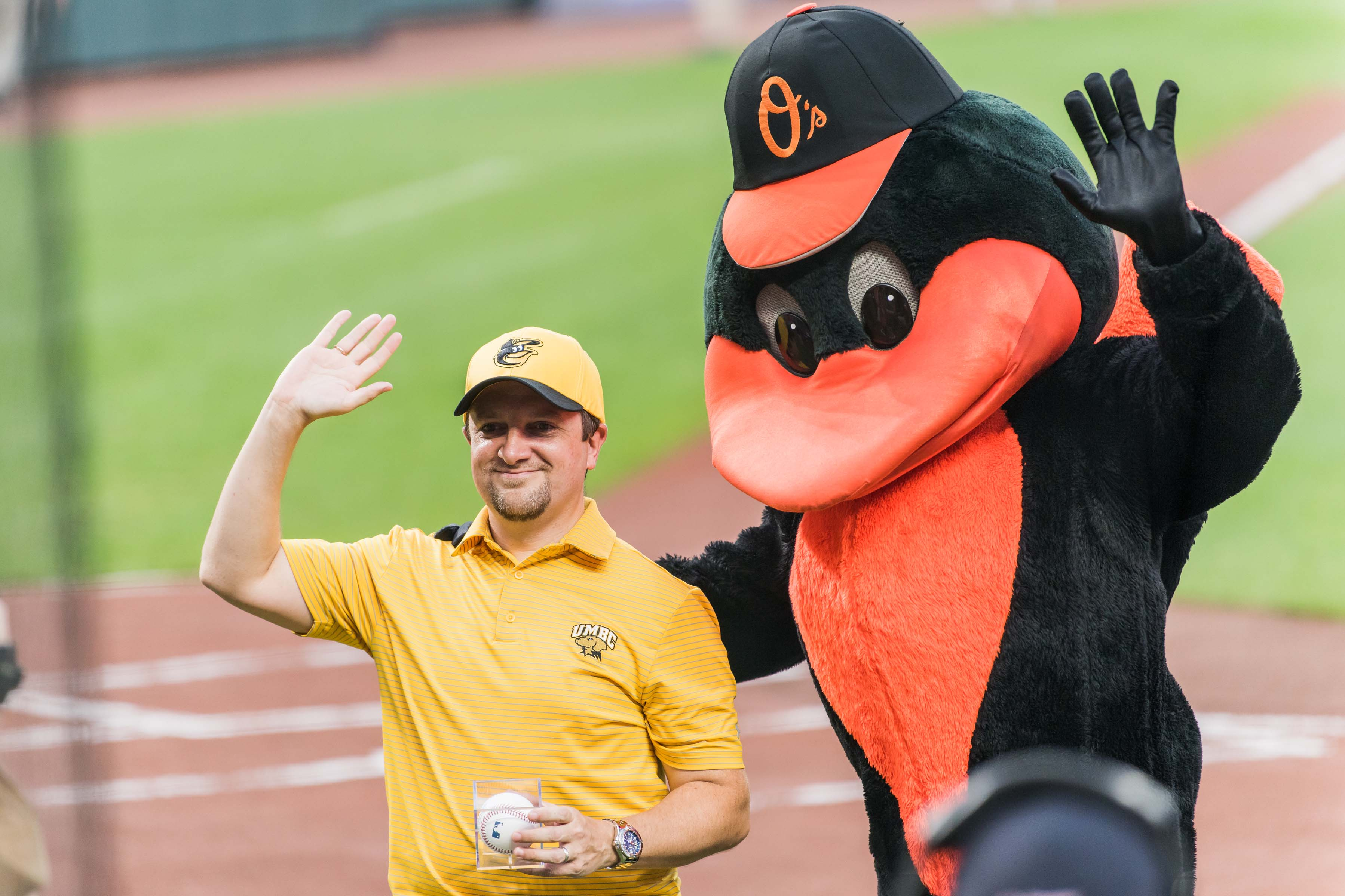 Orioles mascot posing with fan