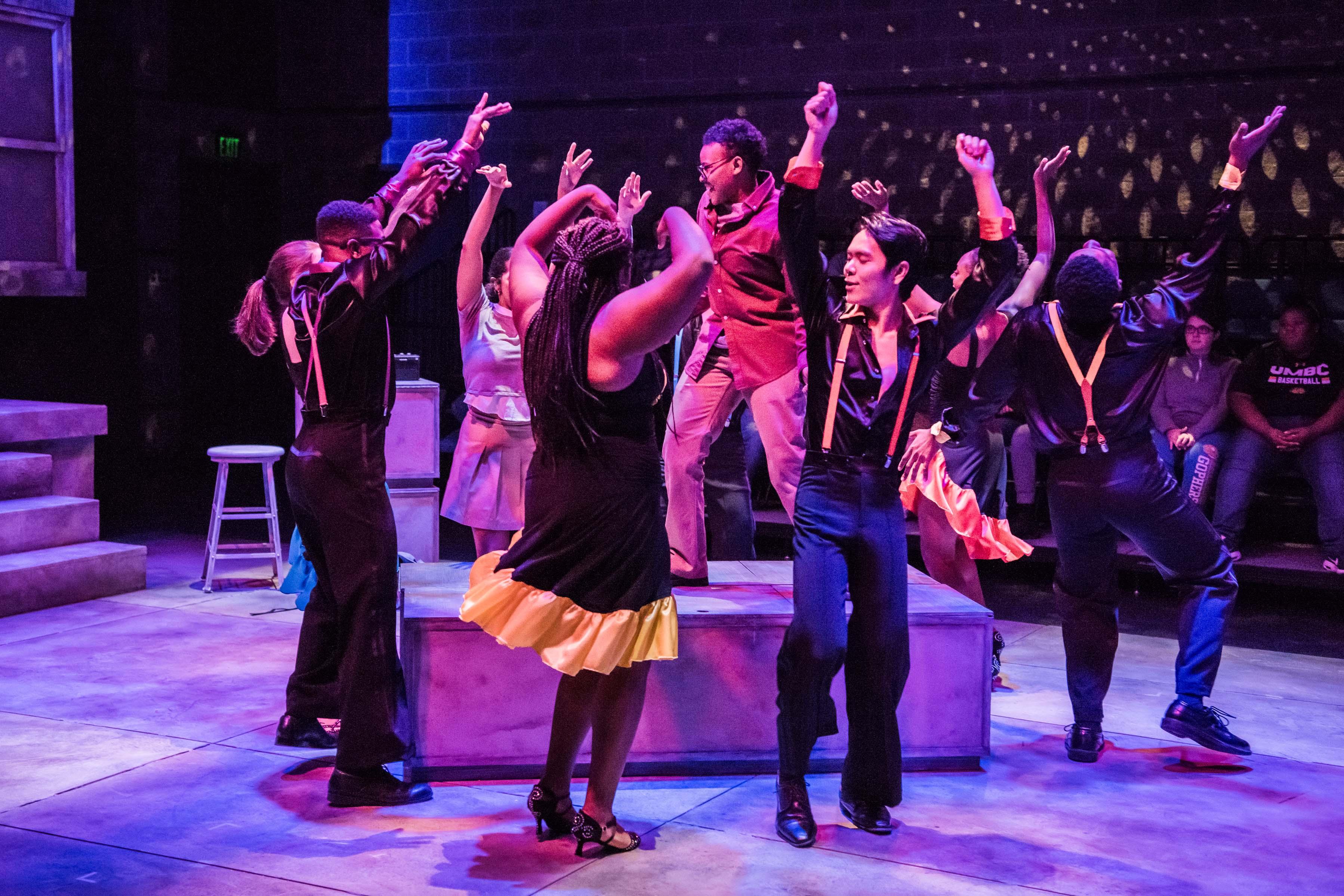 Group dancing around girl on platform at rehearsal
