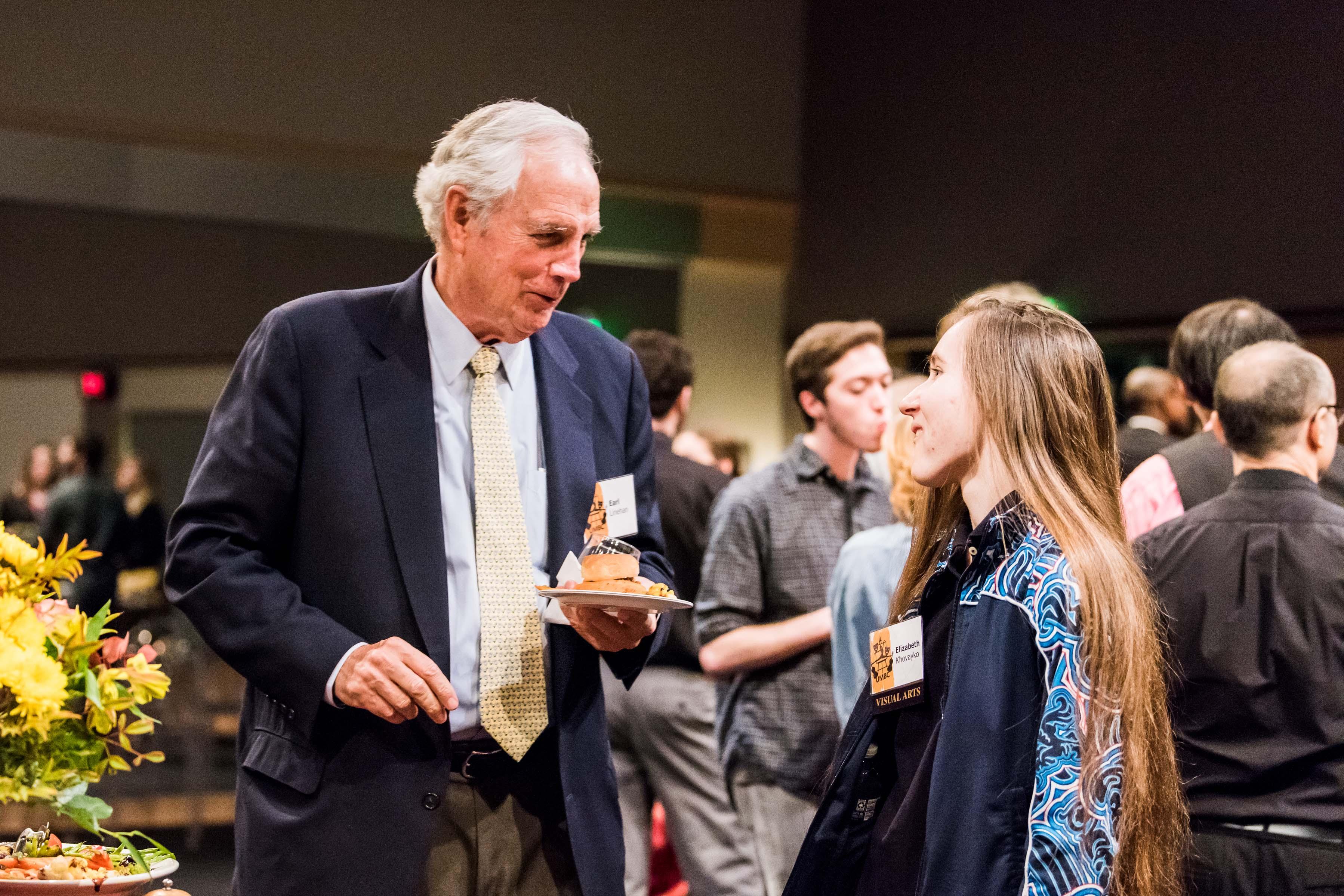 Man talks to elizabeth at linehan scholars reception