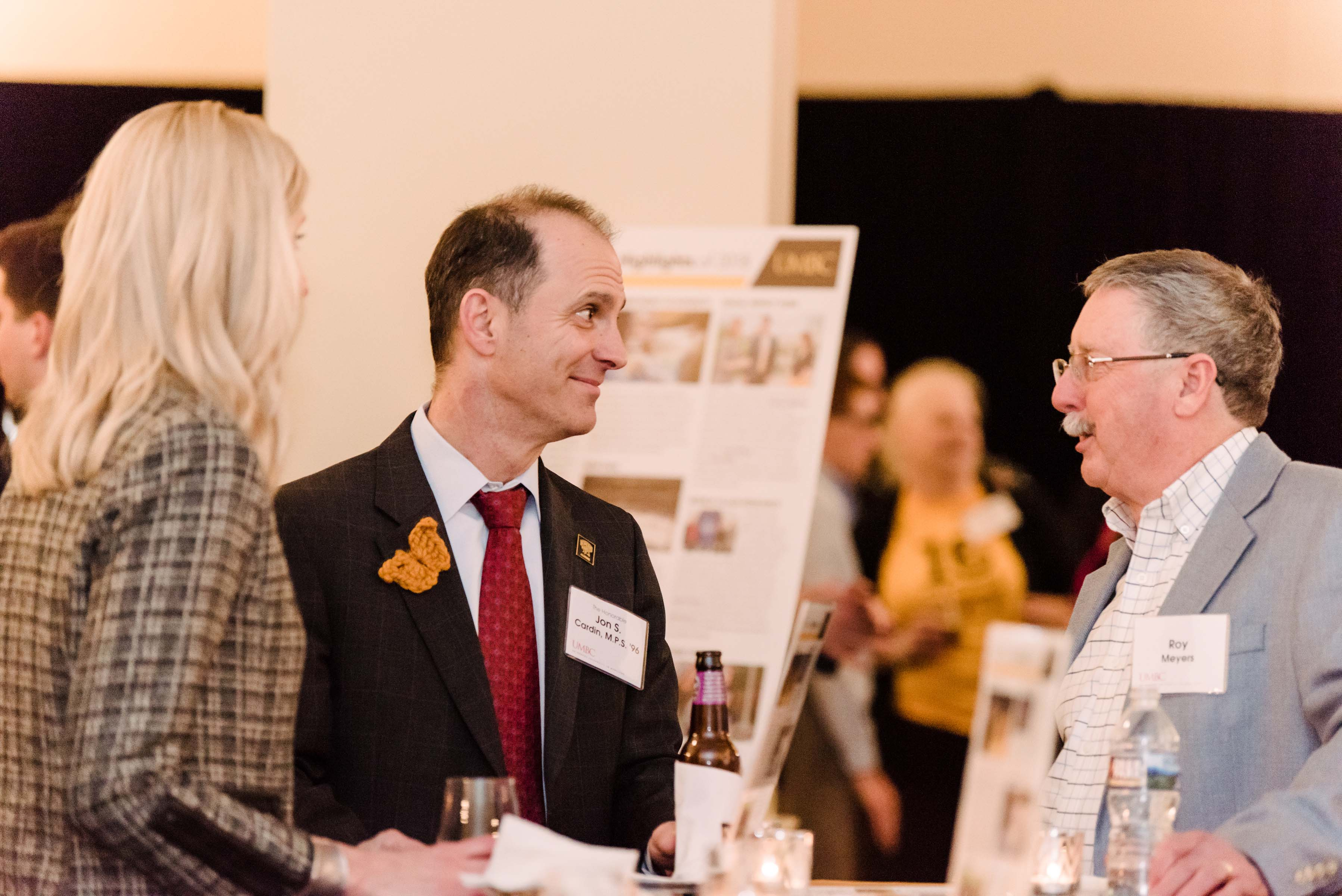 Three people conversing drinks in hand at Annapolis Alumni reception