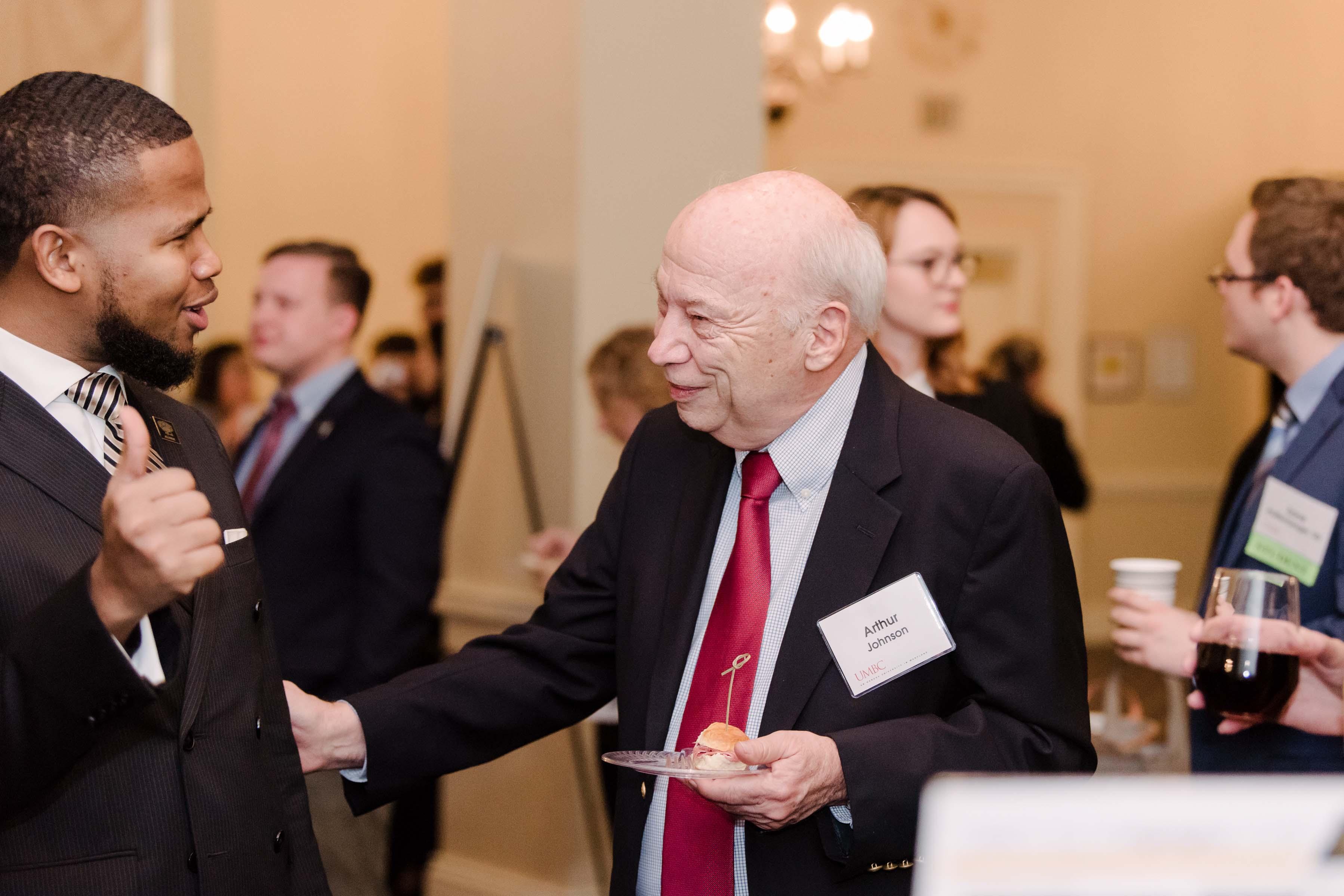 Two men talking animatedly at Annapolis Alumni reception