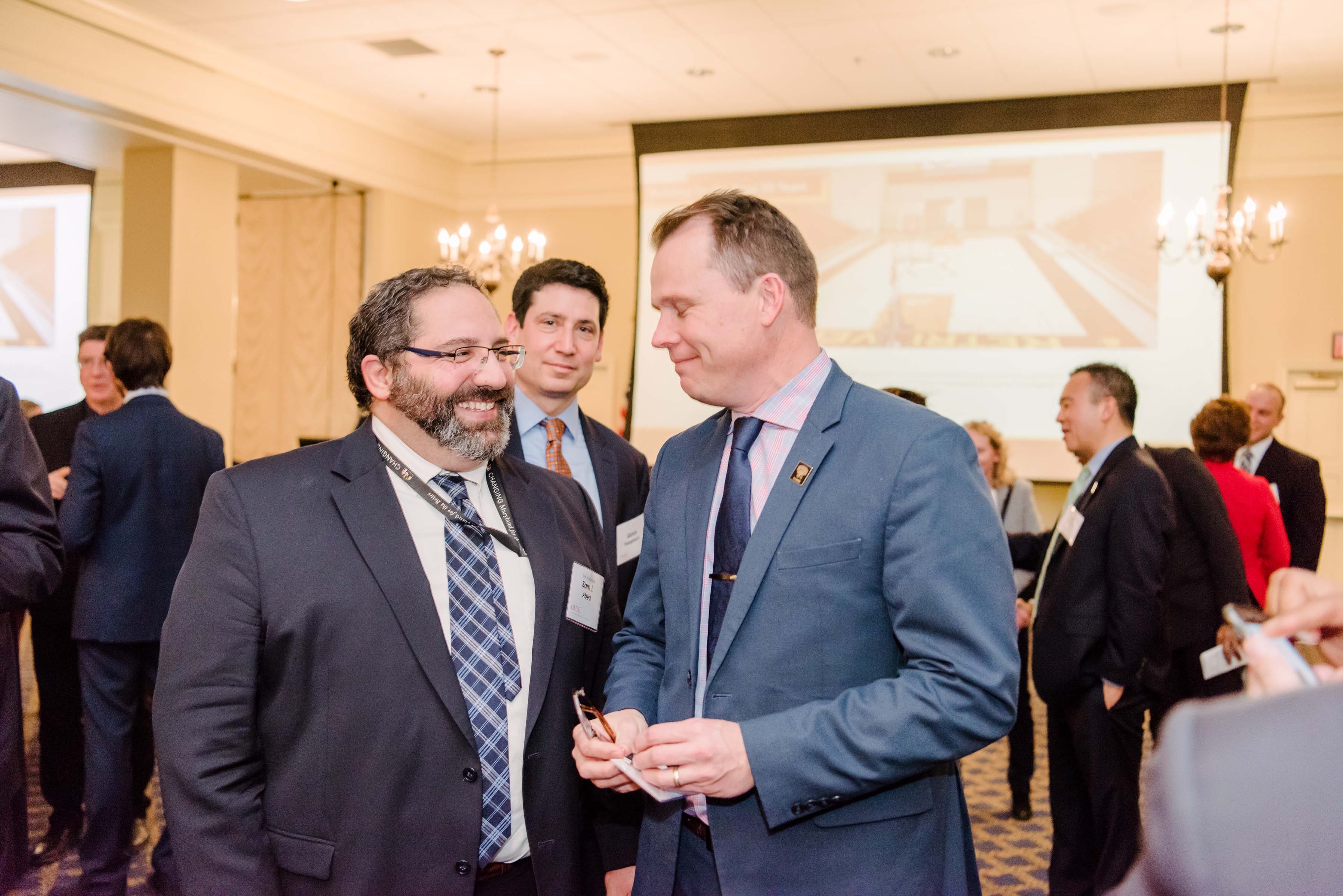 Two men smile at each other at the Annapolis Alumni Reception