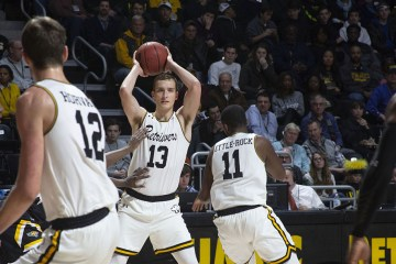 UMBC basketball player holds basketball over his head in game
