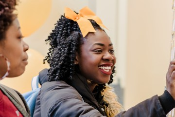 Student with yellow bow interacts with paper on wall for giving day