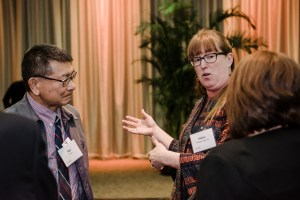 Three people talk in circle at scholarship luncheon