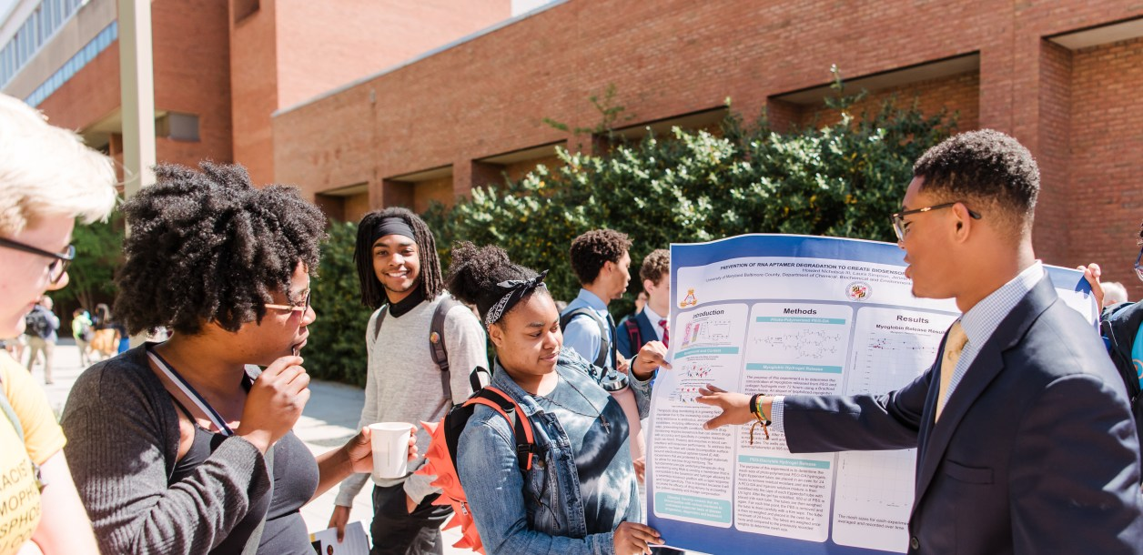 Howard Nicholson '21, continues his poster presentation outside as the Ballroom emptied for an unexpected fire drill.