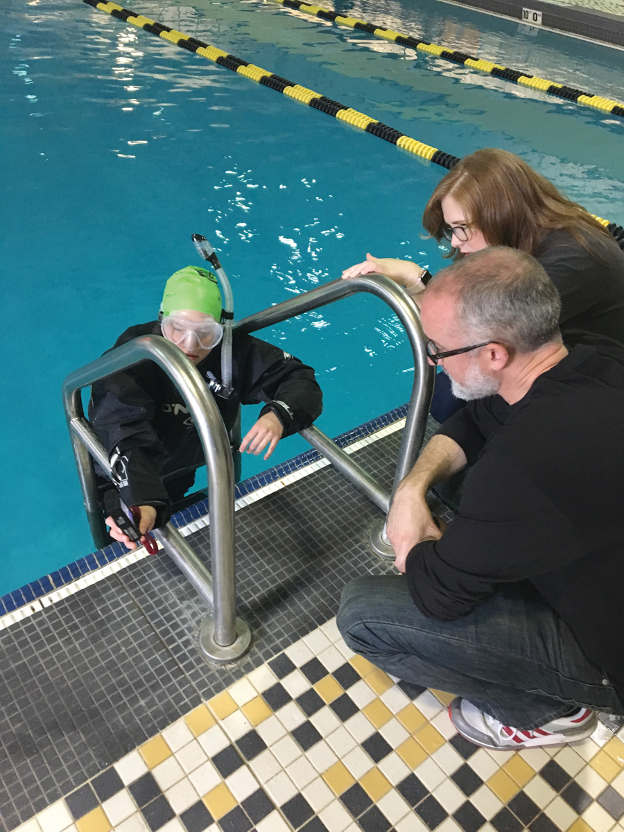 staff members kneel next to pool, Marlayna coming out of pool in dry suit
