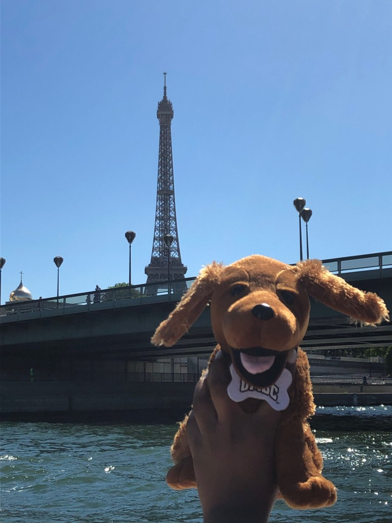 Stuffed True Grit mascot poses in front of the Eiffel Tower.