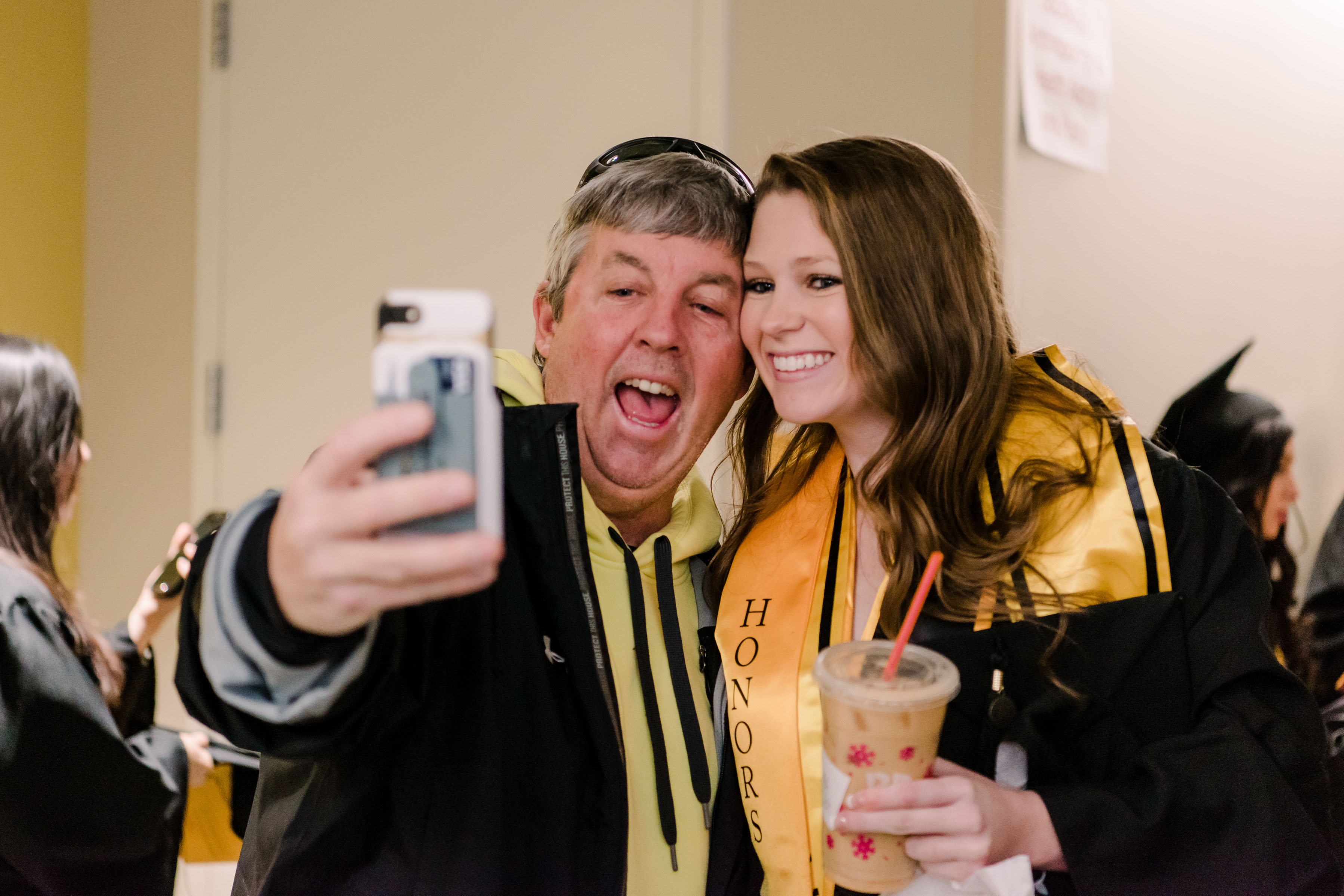 man and graduating student take a selfie together