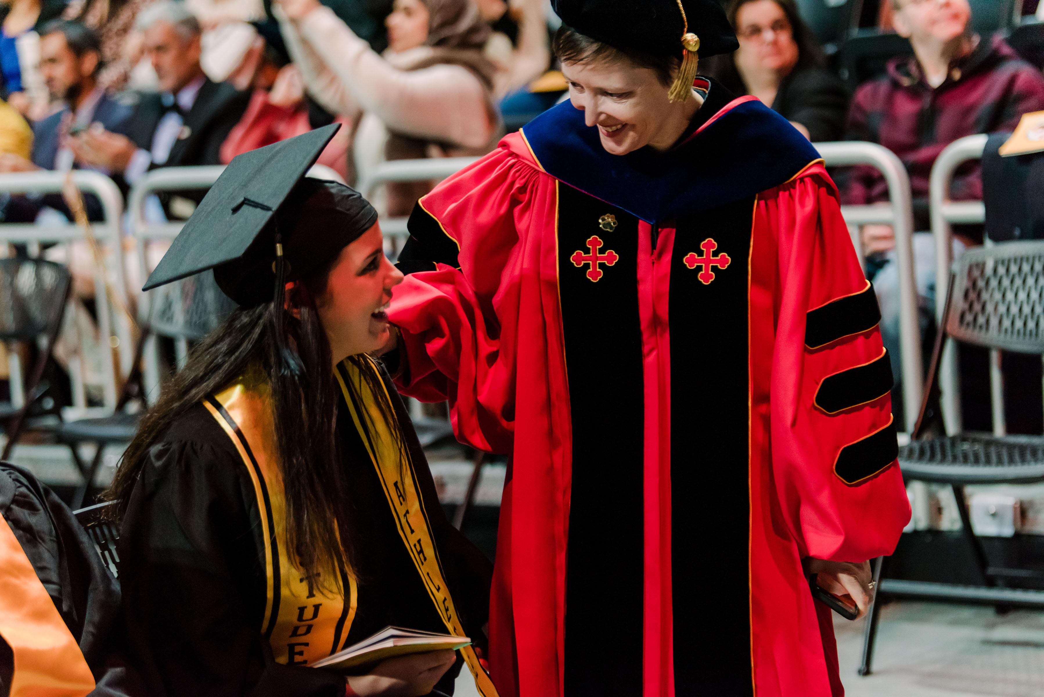 professor and student interact at graduation