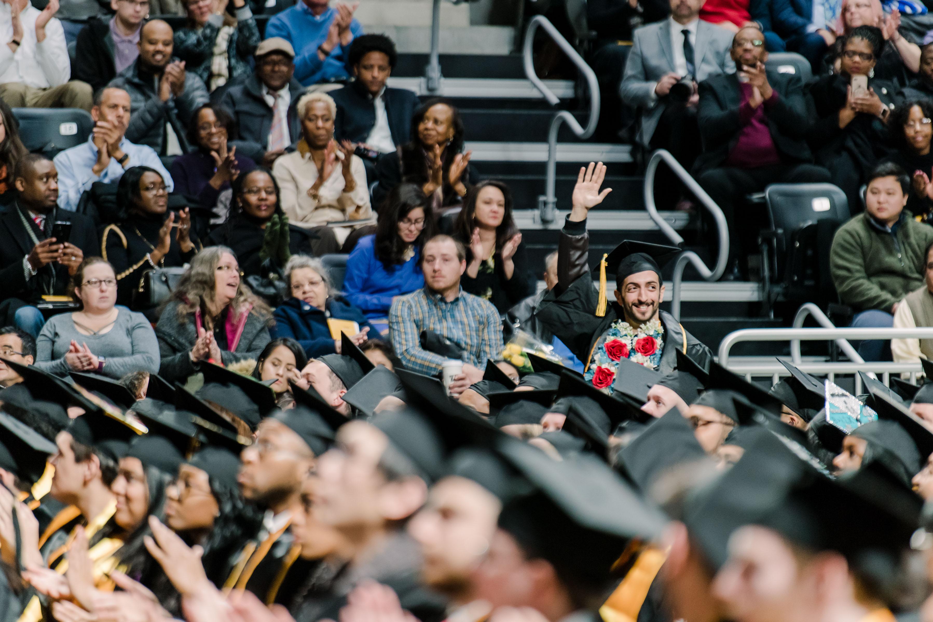 graduating man waves as crowd claps