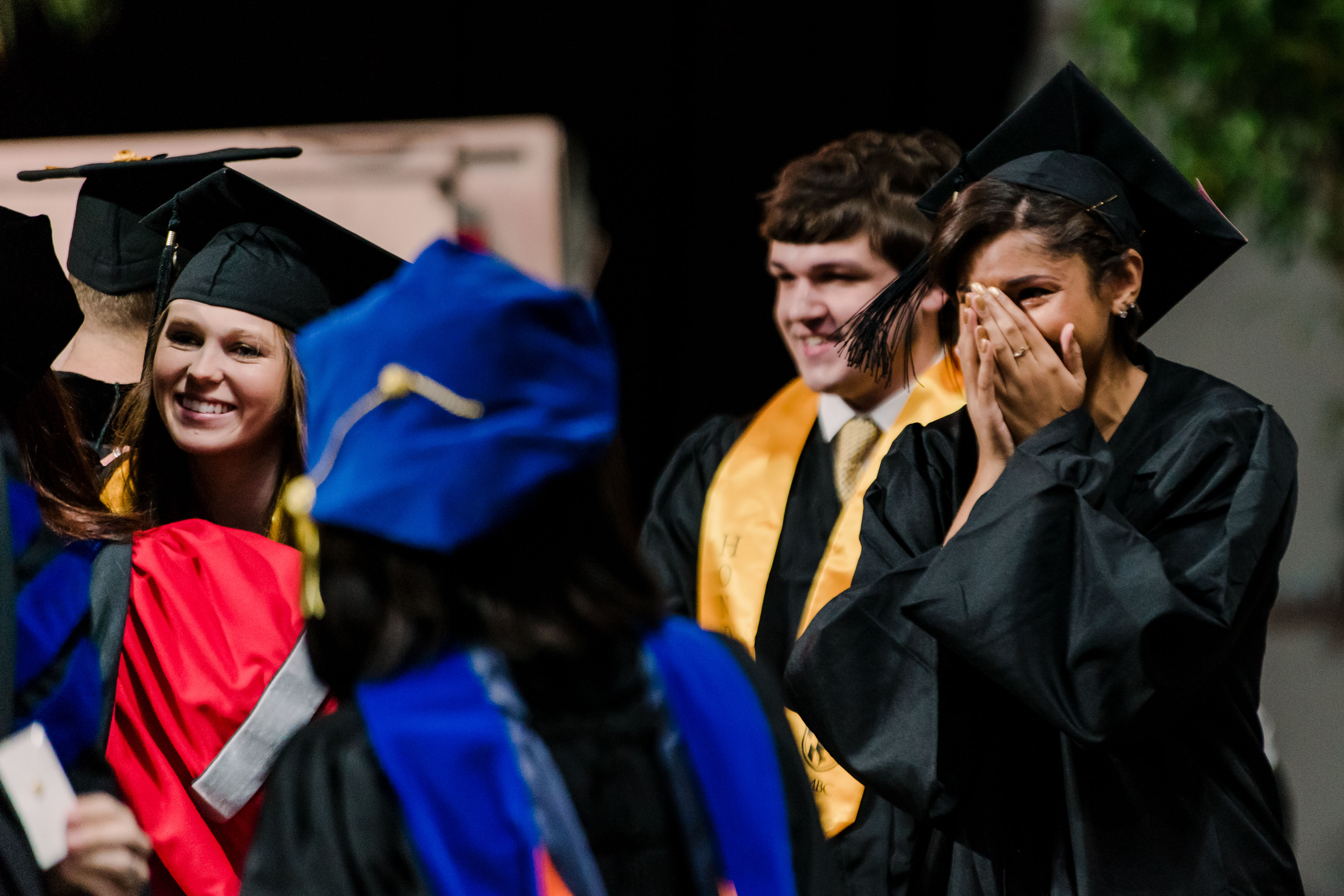 girl surrounded by others in graduation garbs happily covers face