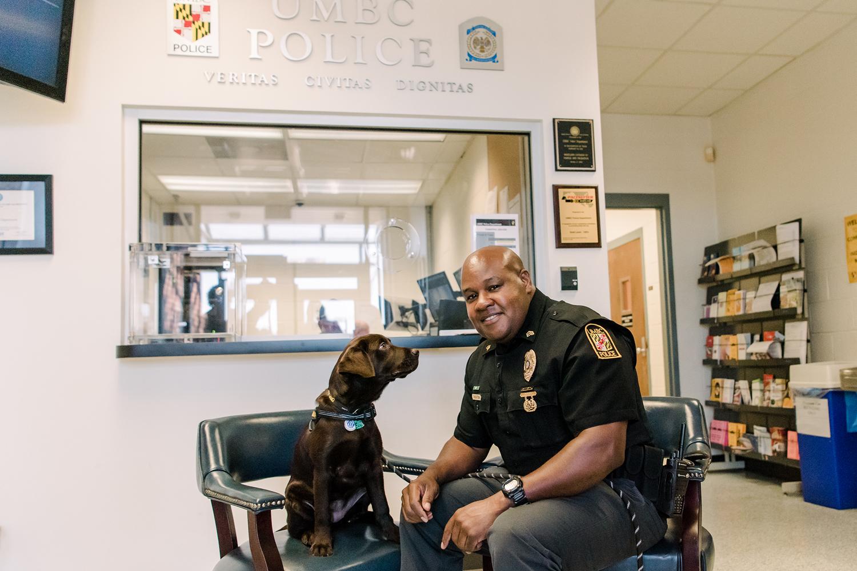 Sergeant Cheatem smiles at the camera as UMBC Police comfort dog looks at him