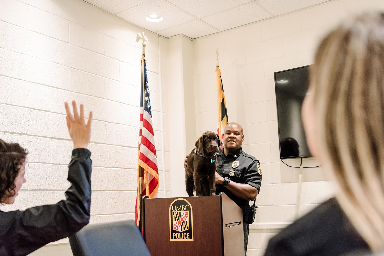 Sergeant Cheatem stands UMBC Police comfort dog on a podium