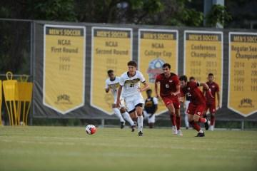 Ryan Becher runs after a ball during a UMBC men's soccer game