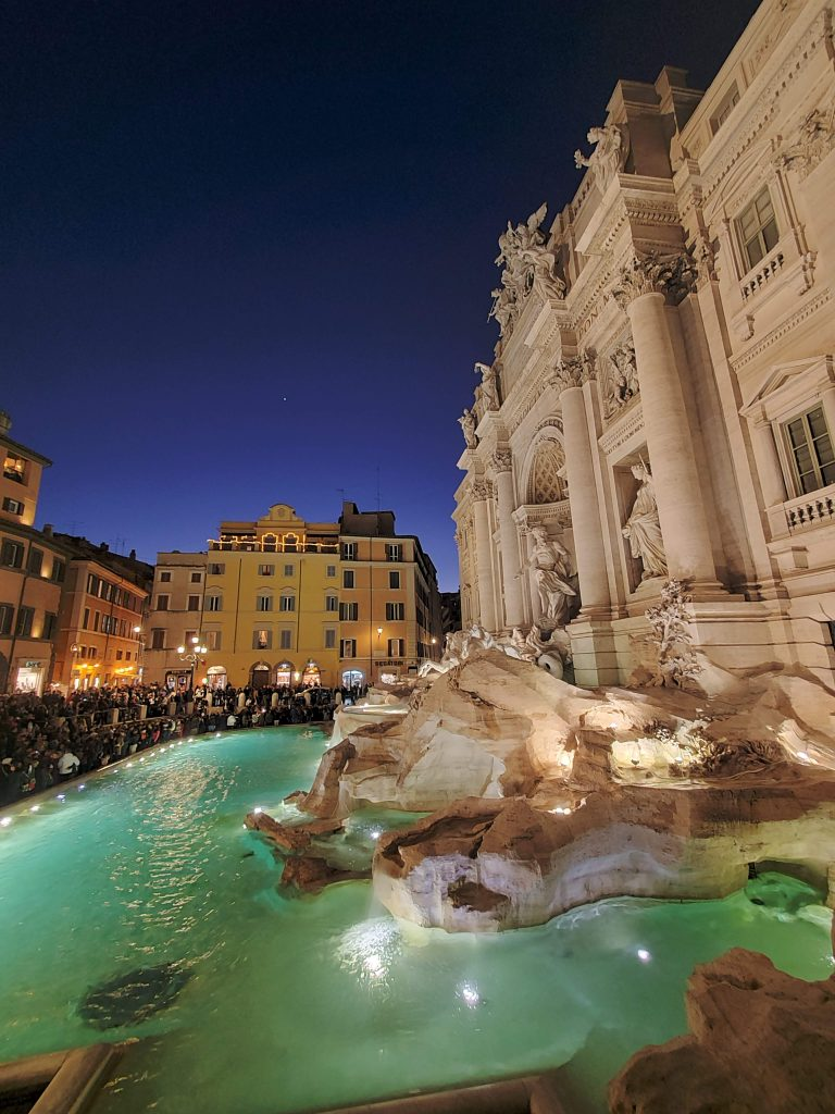 Crowd at the glowing Trevi Fountain.