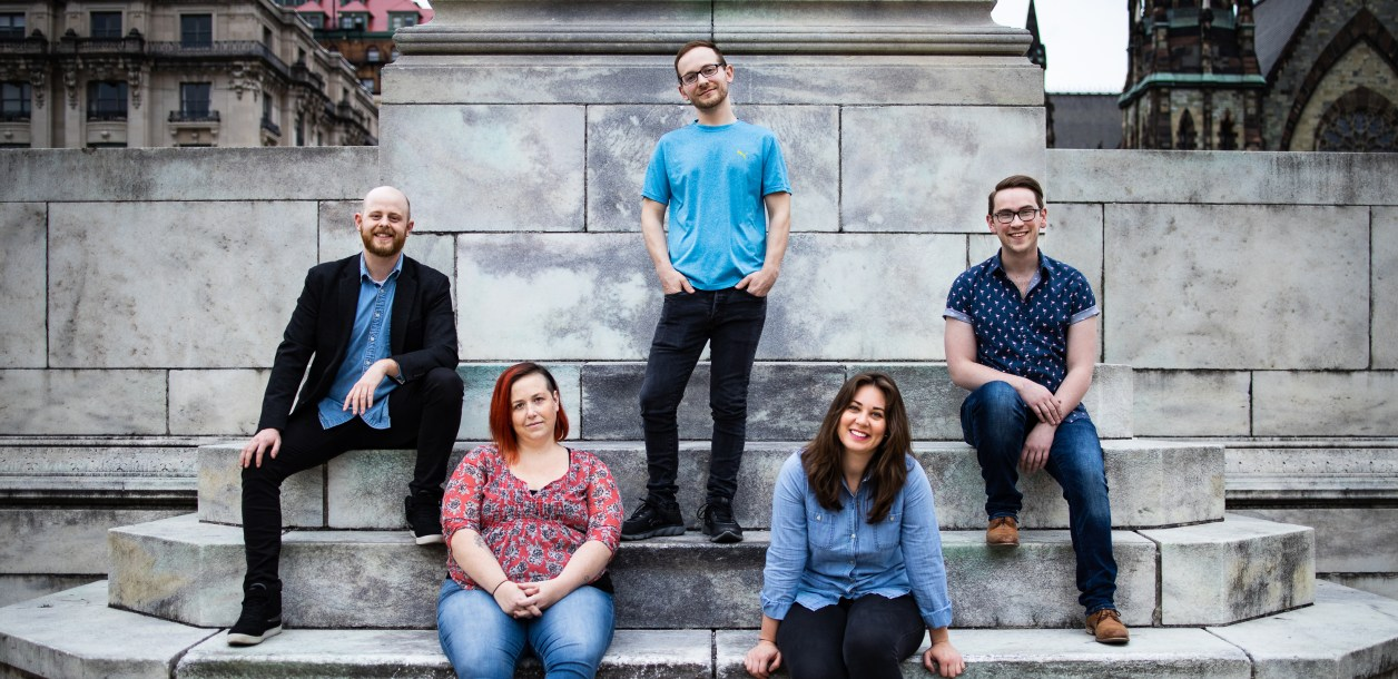 The five alumni that form the Interrobang Theatre Company pose in front of a stone wall