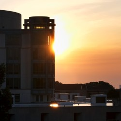 The sun rises behind the UMBC library