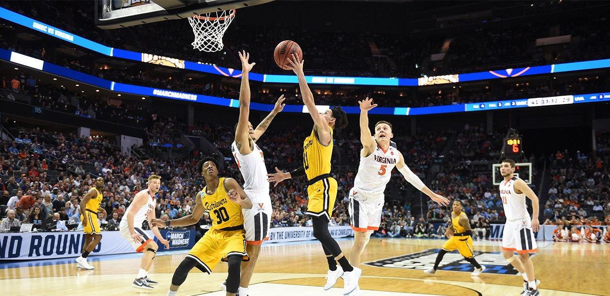 2018 UMBC men's basketball player jumping to make a basket against the University of Virginia team