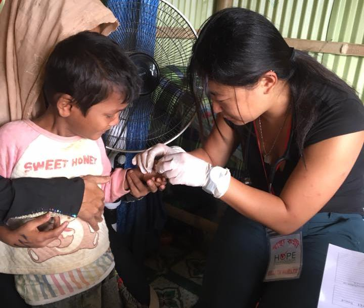 Coco Tang gives treatment to a young boy's hand
