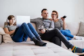 A father, mother and daughter sit on the cough together as the father drinks wine and the daughters is on the computer