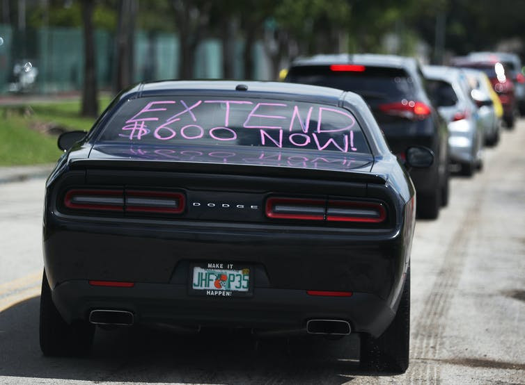 """Black Dodge car with """"Extend $600 now!"""" painted on its back windshield"""