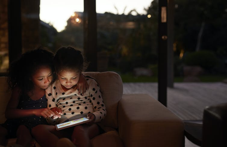 two girls reading on an tablet at night