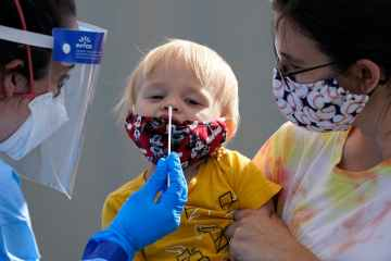 Child gets a COVID-19 nasal swab test done by nurse while mother holds him