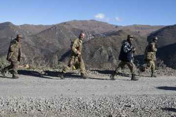 men in military uniforms walk down the road