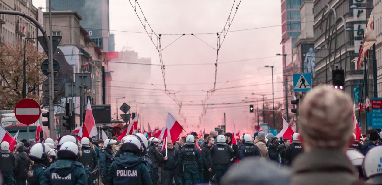 a crowd protests in Poland. You can see the back of their heads and the back of police officers.