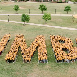 UMBC students stand in crowds to spell out UMBC