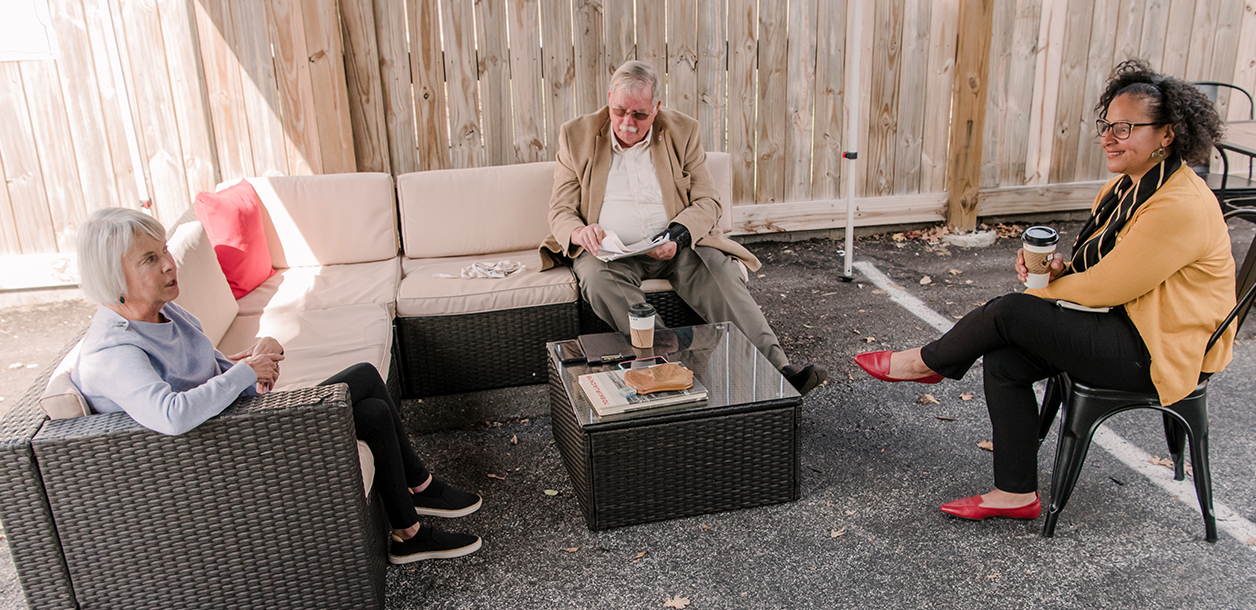 three people sit at a table outdoor to talk