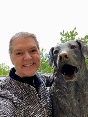 A woman poses with a dog statue.