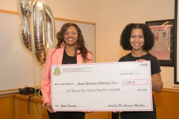 two women holding donation check for scholarship fund