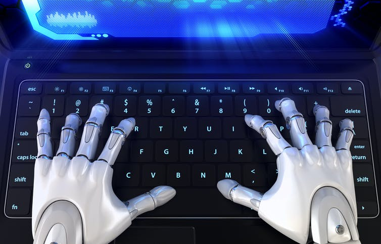 Image of robot typing on computer