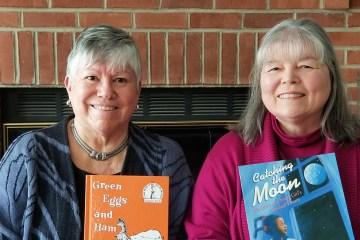 two women holding children's books