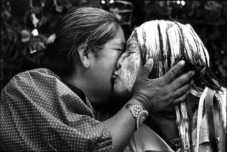 For her project Grrlstories, Pinneo photographed an Apache girl during a strenuous, days-long Apache puberty ceremony. Here the painted 13-year-old kisses her mother after the Sunday sunrise ceremony. The girl prepared for the events by running two miles every day and building herself a hut of saplings.