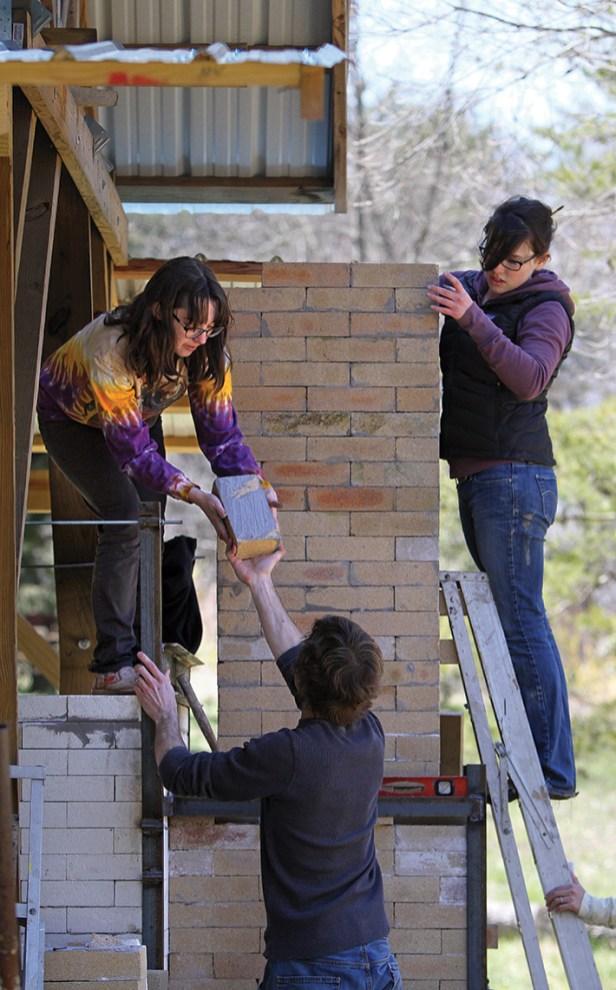 Christina Bendo (in tie-dyed shirt) and Katie Sleyman (on ladder) place kiln bricks.
