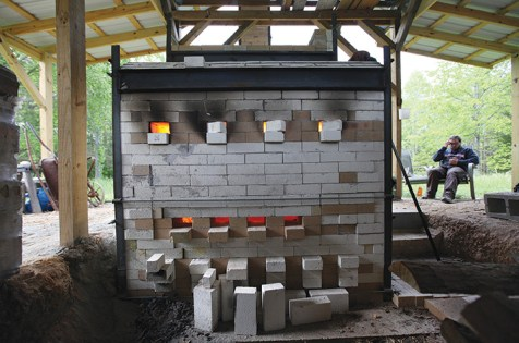 The glow from the firing is seen through planned, adjustable gaps in the bricks.